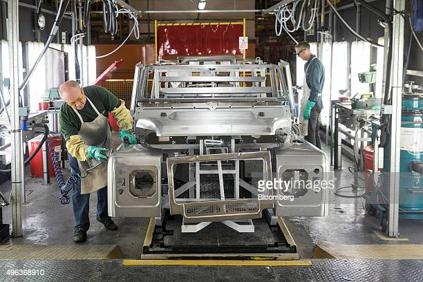 An employee works on the bodywork of a Land Rover Defender automobile at Tata Motors Ltd's Jaguar Land Rover vehicle manufacturing plant in Solihull...