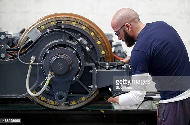 An employee works on the components of a bogie chassis assembly during train carriage manufacturing at AnsaldoBreda SpA's rail car plant in Naples...