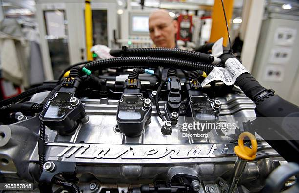 An employee works on the engine of a Maserati Ghibli luxury automobile produced by Maserati SpA at Fiat SpA's Grugliasco factory in Turin Italy on...