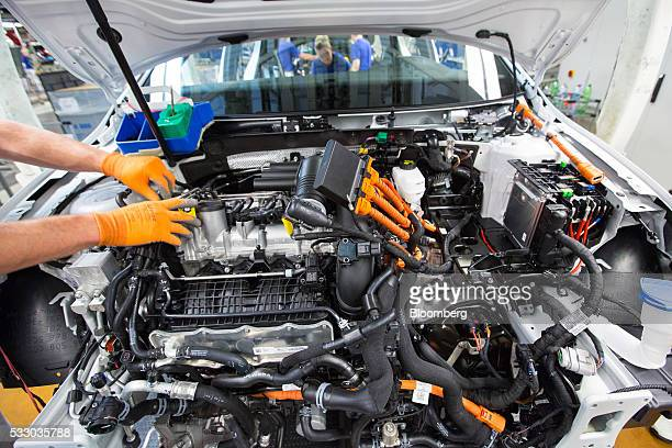 An employee works on the engine of a Volkswagen eGolf electric automobile on the assembly line inside the Volkswagen AG factory in Wolfsburg Germany...