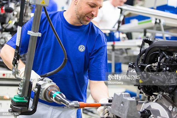 An employee works on the engine of a Volkswagen Golf automobile on the assembly line inside the Volkswagen AG factory in Wolfsburg Germany on Friday...