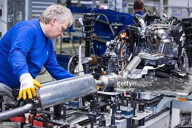 An employee works on the exhaust system of a Volkswagen GTE Golf hybrid automobile inside the Volkswagen AG factory in Wolfsburg Germany on Friday...