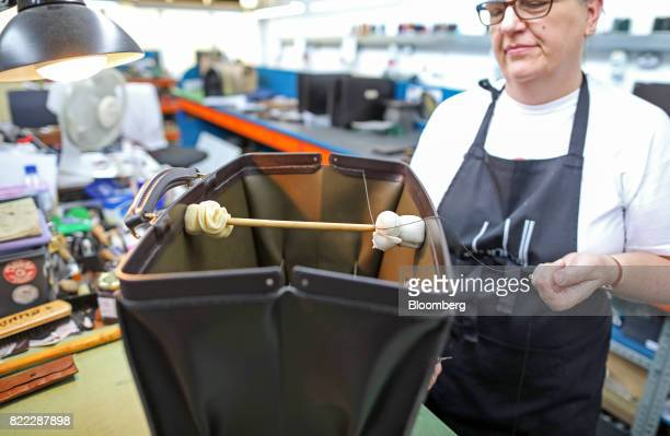 An employee works on the inside of a Wolsley doctors bag at the Alfred Dunhill Ltd London Leather Workshop in London UK on Tuesday July 25 2017...