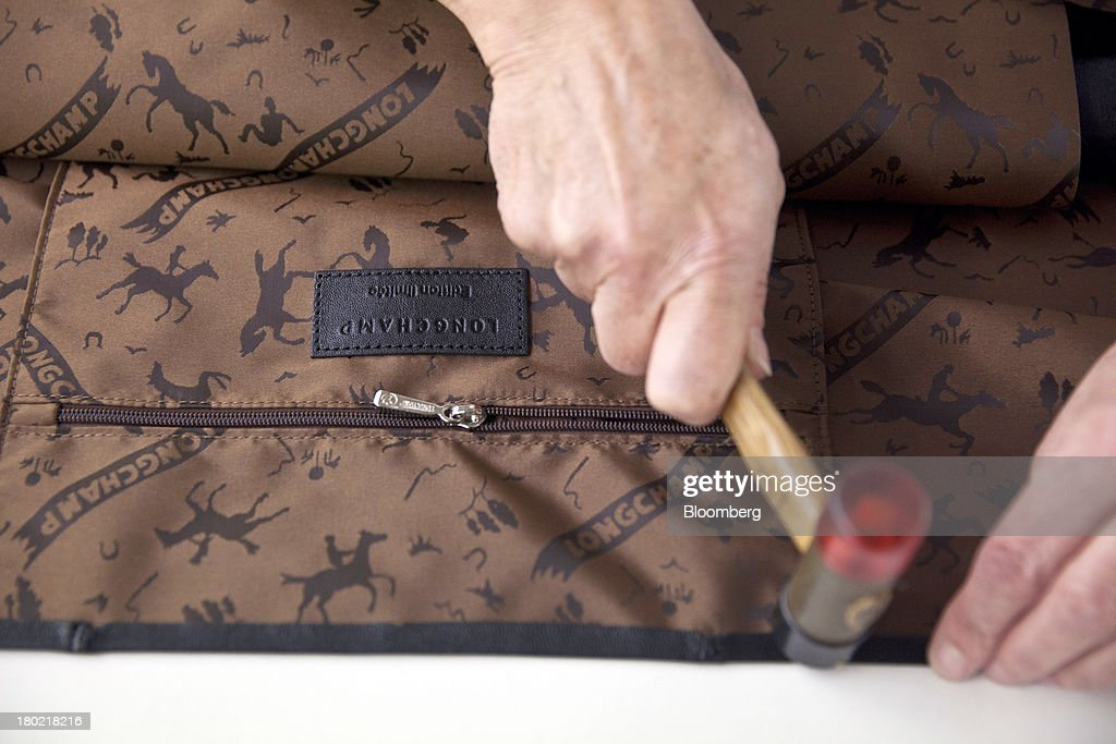 An employee works on the lining for a Le Pliage Cuir bag during the production process at the Longchamp SAS workshop in Segre, France, on Monday, Sept. 9, 2013. Longchamp SAS, the French handbag maker, which is known for foldable Le Pliage nylon tote bags, expects sales in China to rise, Chief Executive Officer Jean Cassegrain said. Photographer: Balint Porneczi/Bloomberg via Getty Images