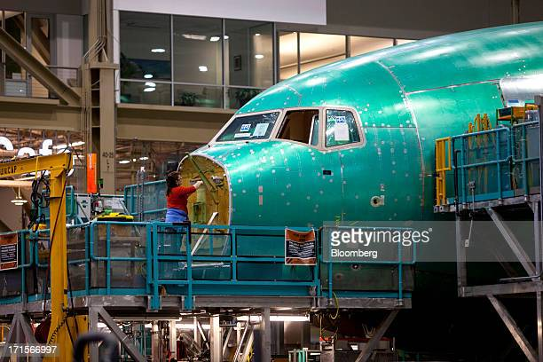 An employee works on the nose of a Boeing Co 777 airplane at the company's facility in Everett Washington US on Tuesday June 25 2013 Boeing Co uses...