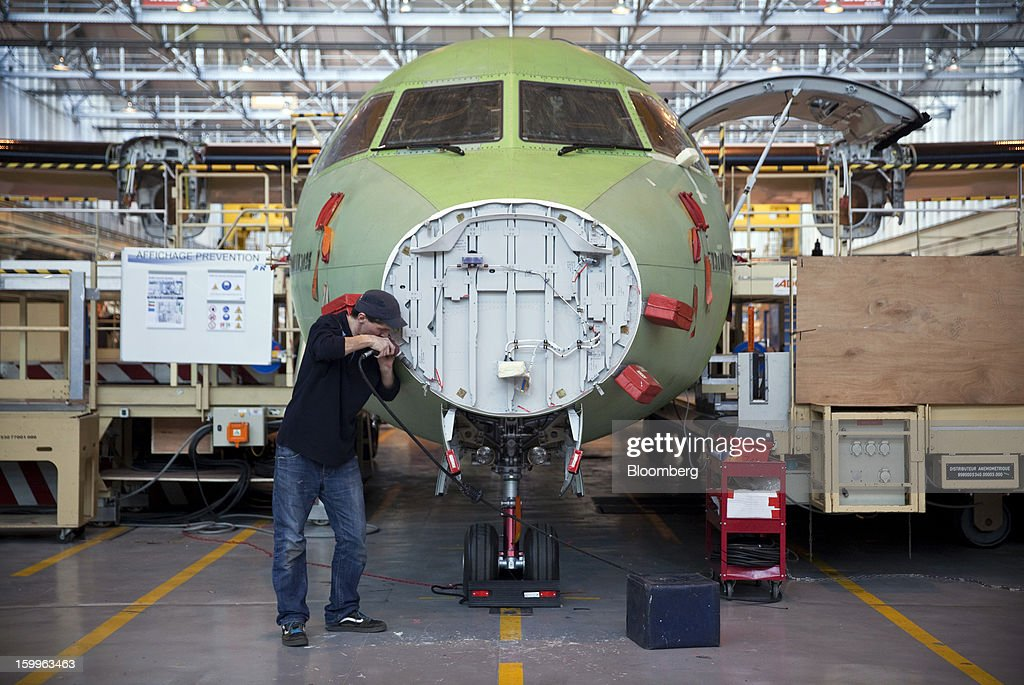 An employee works on the nose section of an ATR-72 turboprop aircraft, manufactured by Avions de Transport Regional (ATR), during assembly at the company's production facility in Colomiers, France, on Wednesday, Jan. 23, 2013. ATR, the world's largest maker of turbo-propeller airliners, reported record profit for 2012, even as it fell short of its shipment target amid production delays. Photographer: Balint Porneczi/Bloomberg via Getty Images
