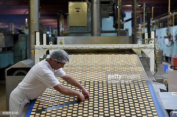An employee works on the production line of the 'petit beurre' biscuit in the factory of French biscuit manufacturer LU in La HayeFouassiere near...