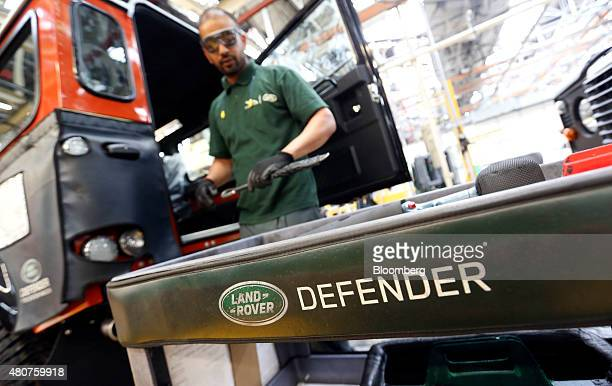 An employee works on the rear of a Land Rover Defender automobile at Tata Motors Ltd's Jaguar Land Rover vehicle manufacturing plant in Solihull UK...