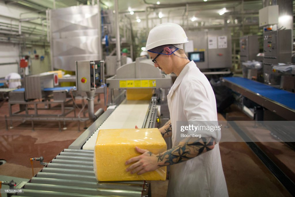 An employee works on the Red Leicester cheese packaging line at Wyke Farms Ltd., in Bruton, U.K., on Friday, Sept. 27, 2013. Wyke Farms, the U.K.'s largest family-owned cheese maker and milk processor, has started using waste from its cows and pigs to generate clean power and help shave as much as 1 million pounds ($1.6 million) a year off its energy bills. Photographer: Simon Dawson/Bloomberg via Getty Images