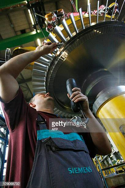 An employee works on the rotor of a Siemens AG Gas Turbine class H at the German industrial giant Siemens historic construction plant on October 12...