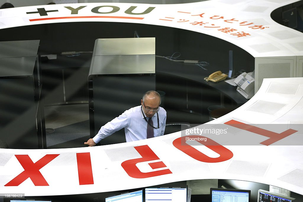 An employee works on the trading floor of the Tokyo Stock Exchange (TSE) on the last trading day of the year in Tokyo, Japan, on Friday, Dec. 28, 2012. Japanese stocks rose, with the Nikkei 225 Stock Average capping its biggest yearly advance since 2005, as the yen weakened after consumer prices and industrial production data fueled speculation the central bank will respond to calls for more stimulus. Photographer: Kiyoshi Ota/Bloomberg via Getty Images