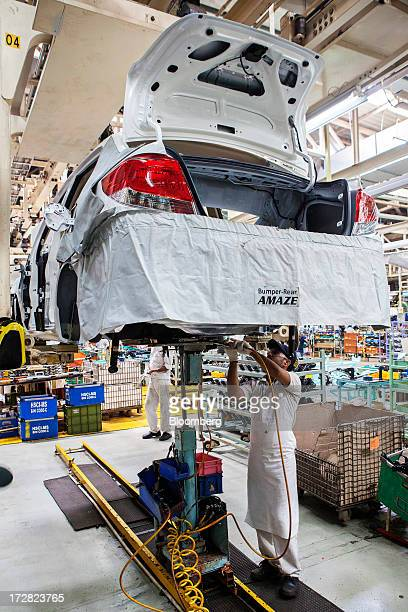 An employee works on the undercarriage of a Honda Motor Co Amaze vehicle on the production line of the Honda Cars India Ltd plant in Greater Noida...
