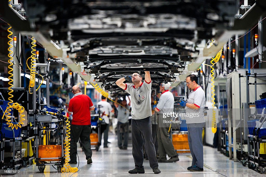 An employee works on the underside of a Seat Altea XL automobile on the assembly line at the headquarters of Seat SA in Martorell, Spain, on Thursday Feb. 28, 2013. Seat will invest 300 million euros a year in the next five years and renew its range of models, Efe said, citing an interview with James Muir, head of the Spanish unit of Volkswagen AG. Photographer: David Ramos/Bloomberg via Getty Images