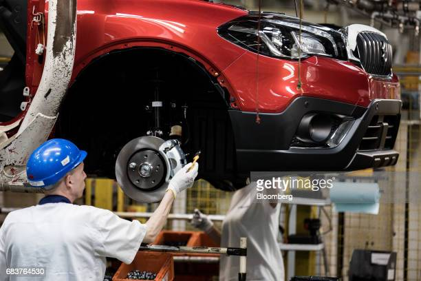 An employee works on the wheel hub of a Suzuki SX4 SCross Crossover automobile on the production line inside the Suzuki Motor Corp plant in Esztergom...