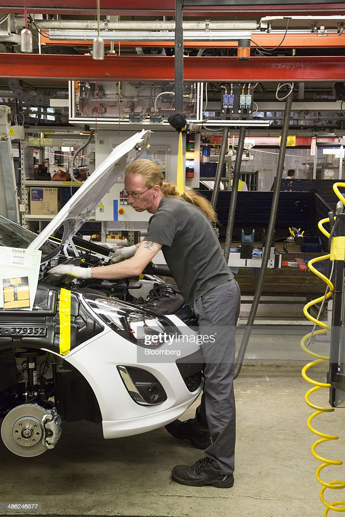 An employee works under the hood of an Opel Corsa automobile at the Adam Opel AG factory, operated by General Motors Co. (GM), in Eisenach, Germany, on Wednesday, April 23, 2014. European sales at Opel and its U.K. sister brand Vauxhall gained 8.5 percent to 226,888 cars in the first quarter, slightly better than the 8.1 percent increase for the market overall, according to ACEA data. Photographer: Martin Leissl/Bloomberg via Getty Images