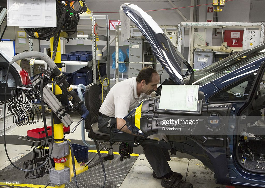 An employee works under the trunk of an Opel Corsa automobile at the Adam Opel AG factory, operated by General Motors Co. (GM), in Eisenach, Germany, on Wednesday, April 23, 2014. European sales at Opel and its U.K. sister brand Vauxhall gained 8.5 percent to 226,888 cars in the first quarter, slightly better than the 8.1 percent increase for the market overall, according to ACEA data. Photographer: Martin Leissl/Bloomberg via Getty Images