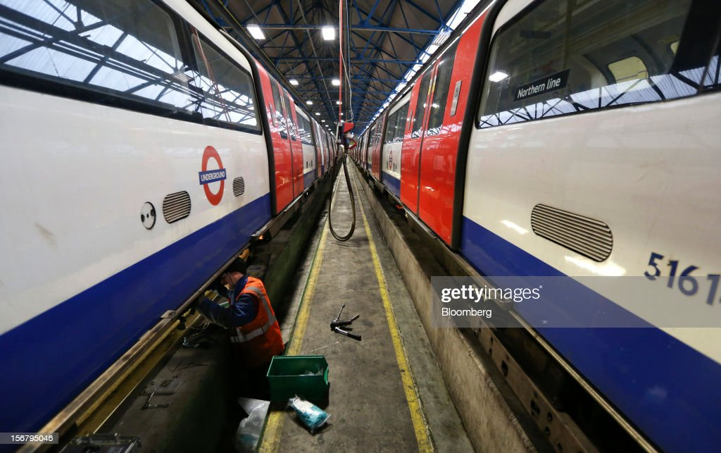An employee works underneath a London Underground Northern Line train at Alstom SA's Traincare Centre in the Golders Green district of London, U.K., on Wednesday, Nov. 21, 2012. Transport for London (TFL), who oversee the U.K. capital's public transport system, issued 300 million pounds ($476 million) of bonds five months ahead of schedule to take advantage of investor demand as it continues its 35 billion-pound transport investment program. Photographer: Chris Ratcliffe/Bloomberg via Getty Images
