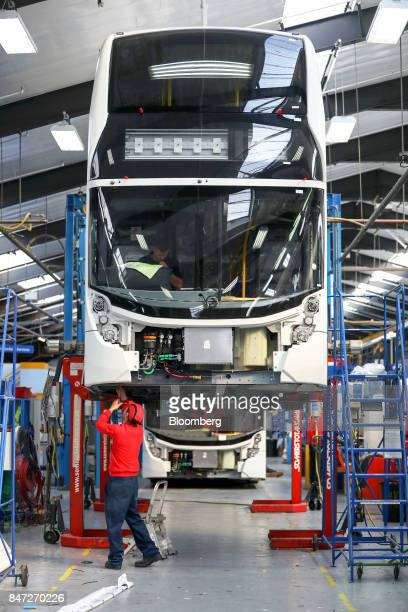 An employee works underneath the drivers cab on an Enviro 400 London bus at the Alexander Dennis Ltd factory in Scarborough UK on Wednesday Sept 13...