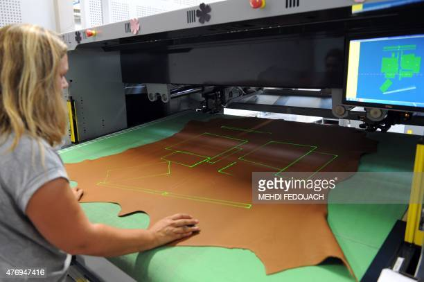 An employee works with a laser cutter at the Maroquinerie de la Tardoire a Hermes workshop specialized in products made with calfskin in Montbron...