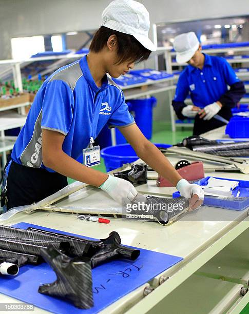 An employee works with carbon fiber parts used in the manufacture of bicycles at the Giant Manufacturing Co Ltd factory in the Kunshan area of Suzhou...