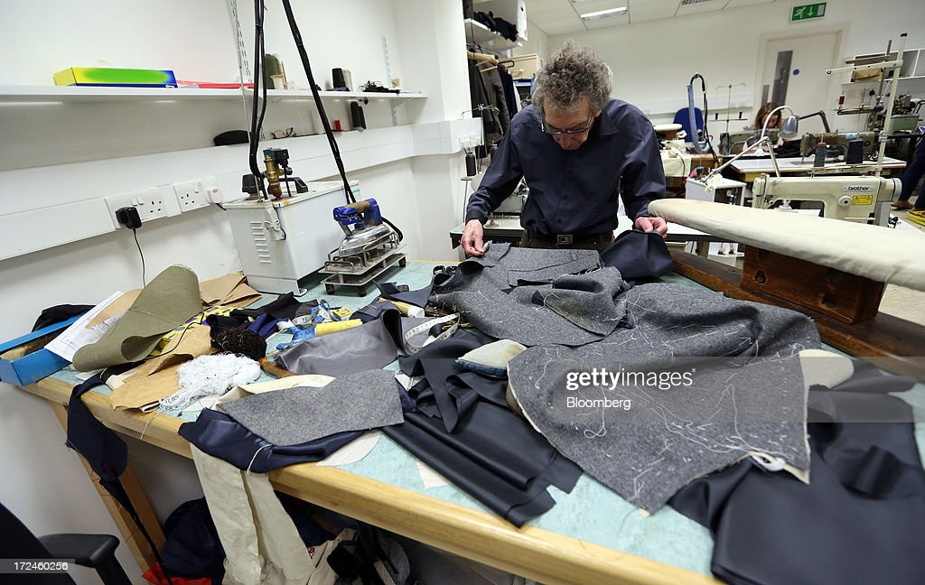 An employee works with material for a suit in the workshop of the tailors Dege & Skinner based on Savile Row in London, U.K., on Tuesday, July 2, 2013. New orders at manufacturers rose for a fourth month in June, led by the textiles clothing industry, while input costs fell for a third month. Photographer: Chris Ratcliffe/Bloomberg via Getty Images