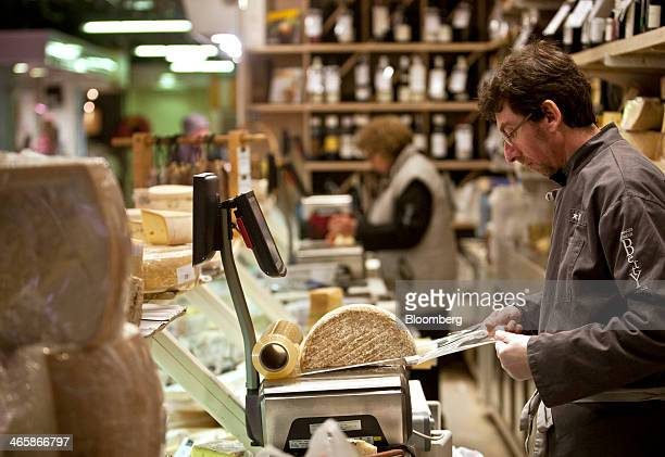 An employee wraps half a wheel of cheese in the Victor Hugo indoor market in Toulouse France on Wednesday Jan 29 2014 Euroregion retail sales...