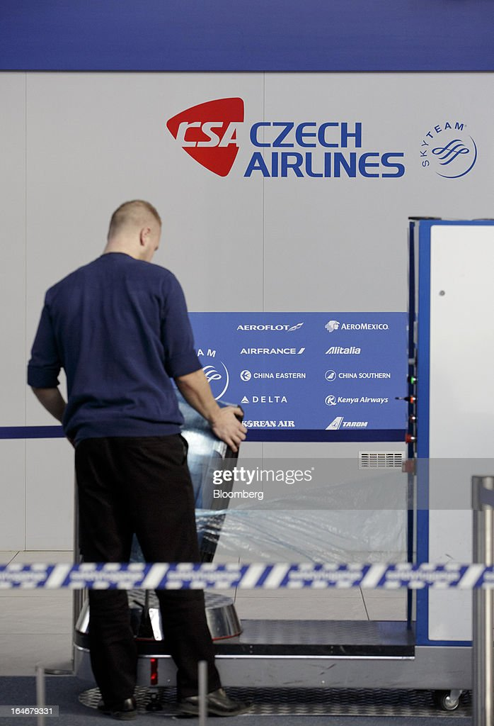 An employee wraps passenger baggage in plastic in front of a Ceske Aerolinie AS (CSA) airline and a Skyteam logo at Vaclav Havel airport in Prague, Czech Republic, on Monday, March 25, 2013. Korean Air Lines Co. pledged to hold its stake in Ceske Aerolinie AS for five years, while CSA's majority owner will refrain from making 'significant' changes in its strategy, according to terms of this week's sale. Photographer: Martin Divisek/Bloomberg via Getty Images
