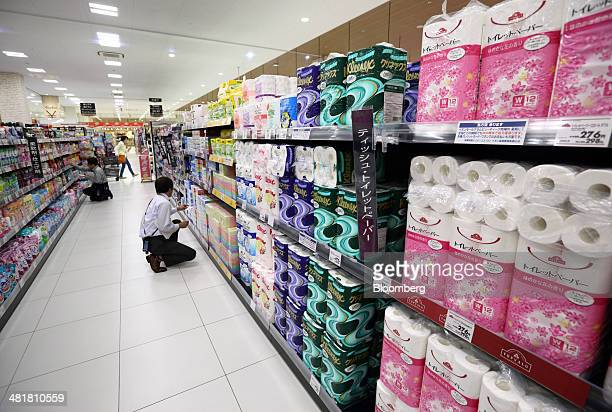 An employees check displays at an Aeon Co supermarket in Chiba Japan on Tuesday April 1 2014 Japan's economy will probably withstand a sales tax...