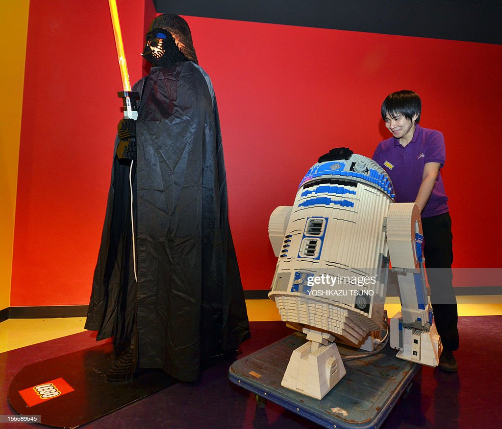 An employees of Lego Japan carries the R2-D2 robot made Lego blocks next to Darth Vader , characters of US movie Star Wars in Tokyo on November 5, 2012 at the Legoland Discovery Center Tokyo. The characters of the Star Wars saga, set to be revived from 2015 under new owners Disney, will be displayed from November 6. AFP PHOTO / Yoshikazu TSUNO