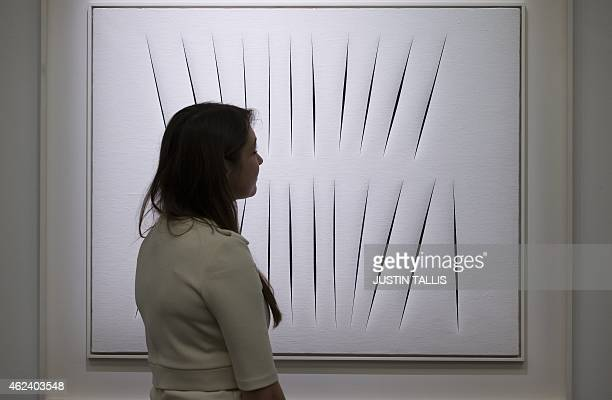 An employees of Sotherby's auction house studies 'Concetto Spaziale Attese' by Lucio Fontana during a press preview in London on January 28 ahead of...