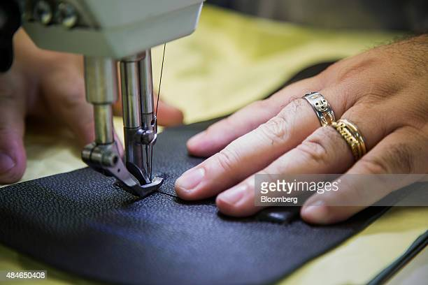 An employees sews a piece of leather for a handbag at the Justin Paul Inc manufacturing facility inside the Brooklyn Navy Yard in the Brooklyn...