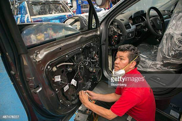 An employees works on the interior of a car door at Ballistic Protection Co's armored car workshop in Mexico City Mexico on Tuesday April 29 2014...