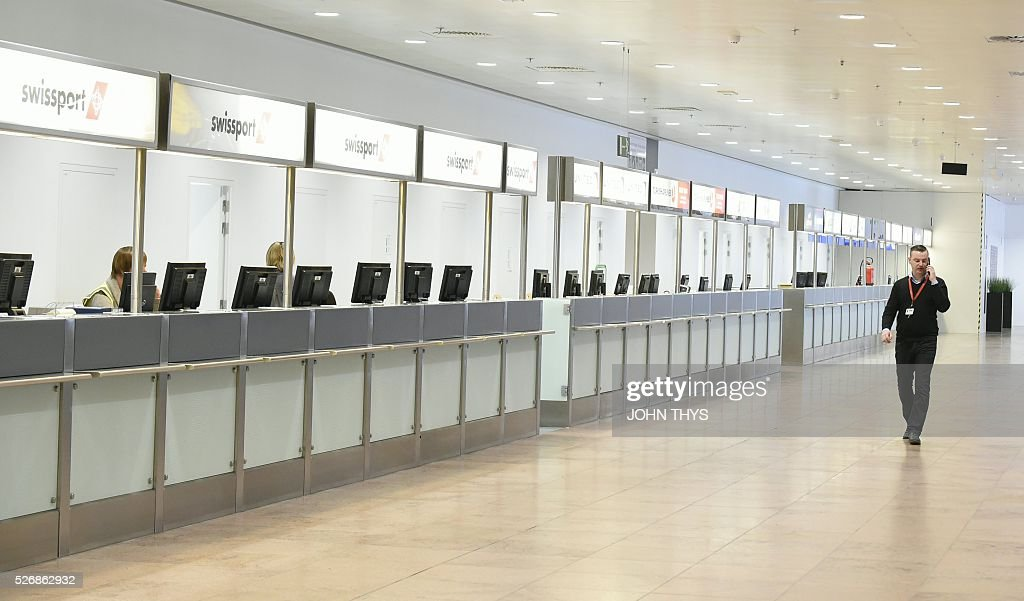 An employer walks during the partial reopening of the departure hall of Brussels Airport in Zaventem on May 1, 2016, after it was badly damaged in twin suicide attacks on March 22, that killed 16 people. A total of 32 people were killed and more than 300 wounded in coordinated suicide bombings at the airport and a metro station in central Brussels on March 22 in Belgium's worst ever terror attacks. / AFP / JOHN