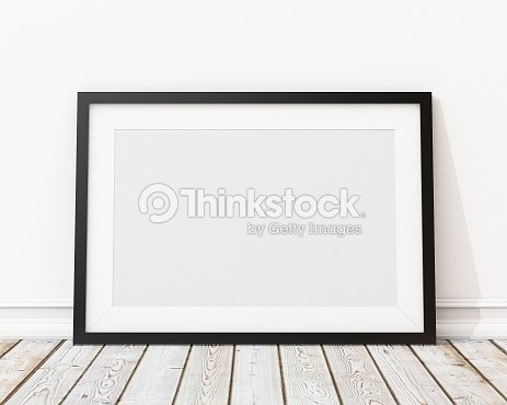 An empty black picture frame leaning against a wall : Stock Photo