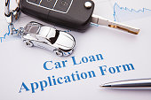 An empty car loan form with car key and a pen