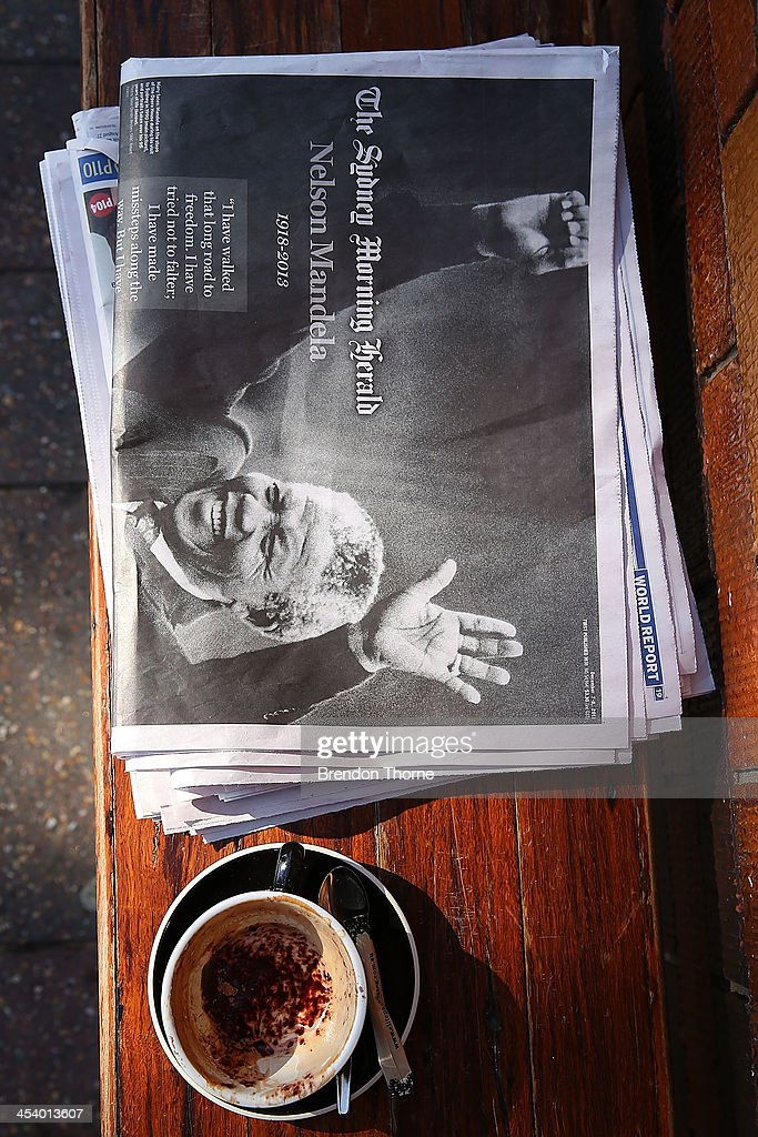 An empty coffee sits on a bench next to an Australian newspaper reporting on the death of former South African President Nelson Mandela on December 7, 2013 in Sydney, Australia. Mandela was a leader that helped conquer apartheid in racially divided South Africa after being jailed for his activism for decades. He was South Africa's first black president. He died yesterday at the age of 95.