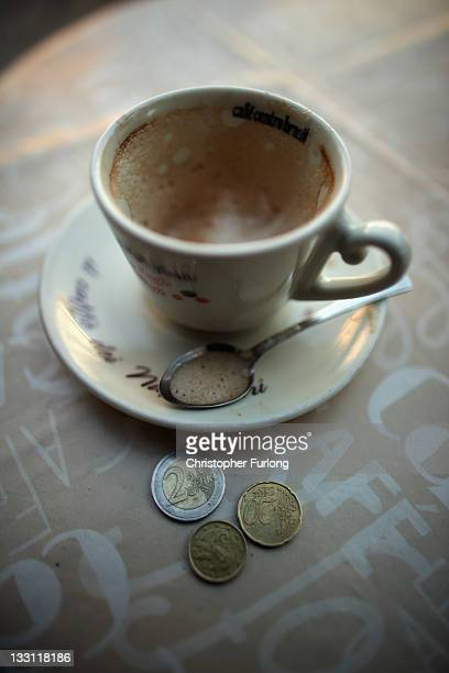 An empty cup of cappuccino and loose euro coins sits on the table of a cafe in central Naples on November 17 2011 in Naples Italy Italy's new PM...