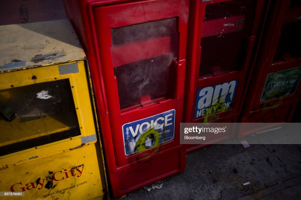 An empty distribution box for The Village Voice, center, is seen in the East Village neighborhood of New York, U.S., on Tuesday, Aug. 22, 2017. Peter Barbey, owner of The Village Voice since 2015, has decided to no longer produce a print edition of the alt-weekly publication. The company's announcement, made Tuesday afternoon, came as a surprise, a shock and a disappointment to the larger media industry on Twitter. Photographer: Michael Nagle/Bloomberg via Getty Images