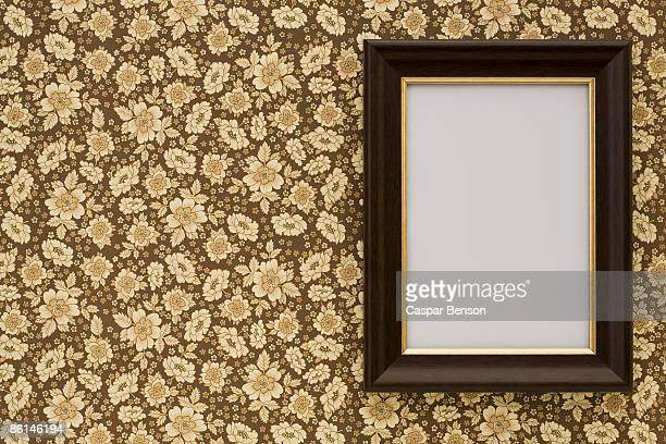 An empty frame hanging on wallpaper