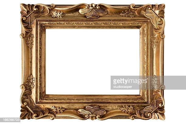 An empty gold antique picture frame over a white background