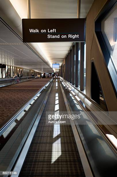 An empty, moving walkway at an has instructions on how to use it.