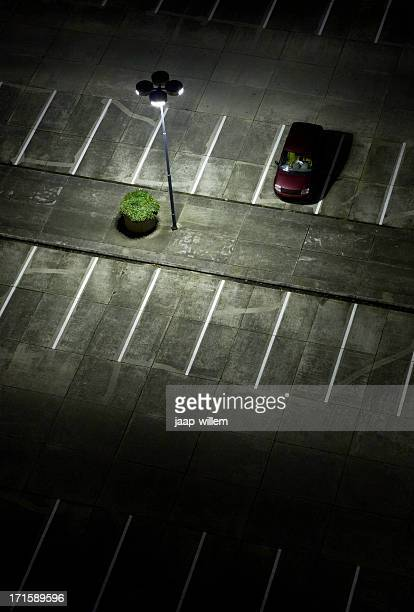 An empty parking lot at night with one red car