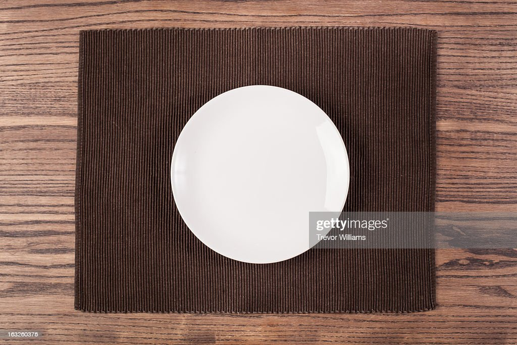 An empty plate on a wooden table