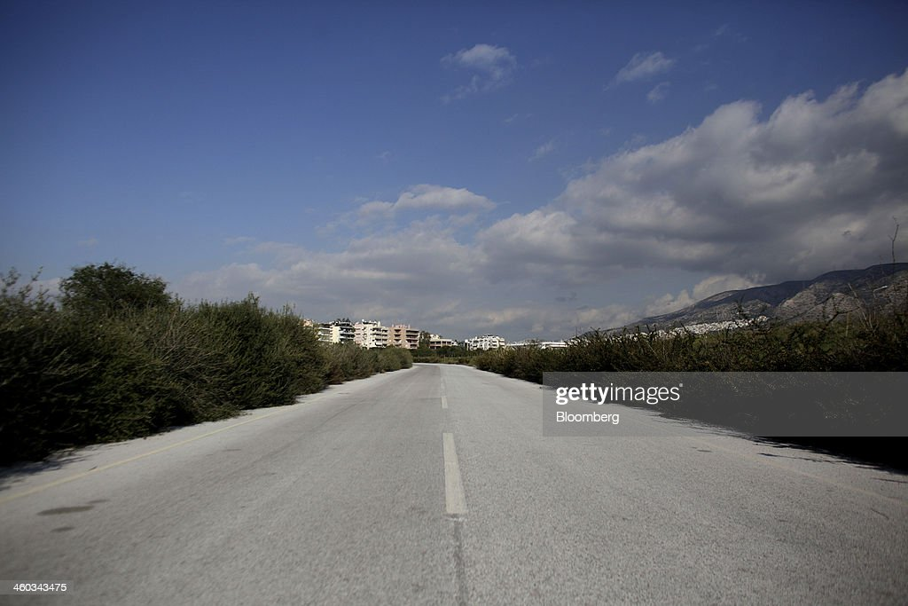 An empty road leads to residential apartments near the former Athens International Airport in the Hellenikon district of Athens, Greece, on Friday, Dec. 3, 2014. Hellenikon is the largest of Greece's land development projects, three times the size of the Principality of Monaco. Photographer: Kostas Tsironis/Bloomberg via Getty Images