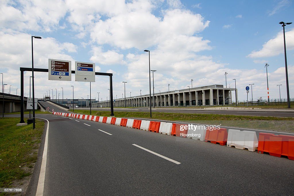 An empty road sits outside the under construction Berlin Brandenburg International Willy Brandt Airport in Schoenefeld, Germany, on Monday, May 3, 2016. The massively overbudget airport was planned to open in 2010 and handle 27 million passengers a year, crowning Berlin as the continent's 21st century crossroads. Photographer: Krisztian Bocsi/Bloomberg via Getty Images