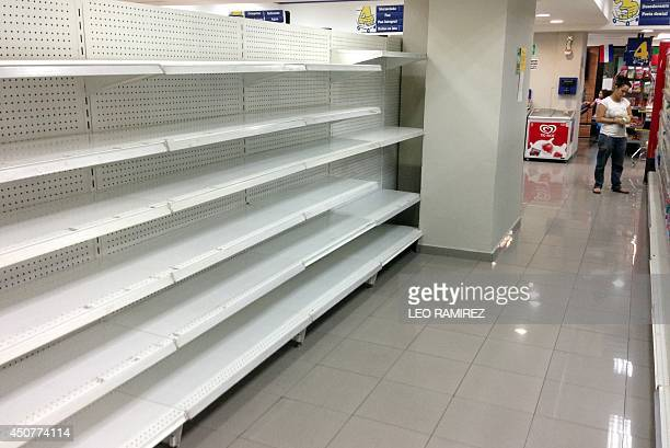 An empty shelf inside a private market in Caracas on June 17 2014 Acetone hair colorants deodorant razors makeup and even coffins are some of the big...