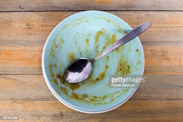 An empty soup bowl with a spoon