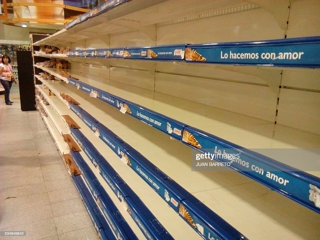 An empty supermarket is pictured in Caracas on May 28, 2016. The shortage of basic foodstuffs in Venezuela exceeds 80 percent, a survey revealed. / AFP / JUAN