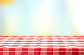 An empty table with a red checkered tablecloth and an pastel colorful natural background on a  sunny day. For your food and product display montage. Concept food.