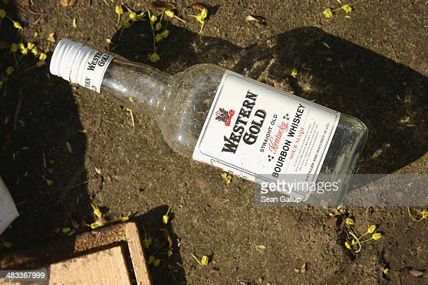 An empty whiskey bottle is among detritus lying on the ground at the former temporary refugee camp at Oranienplatz in Kreuzberg district after riot...